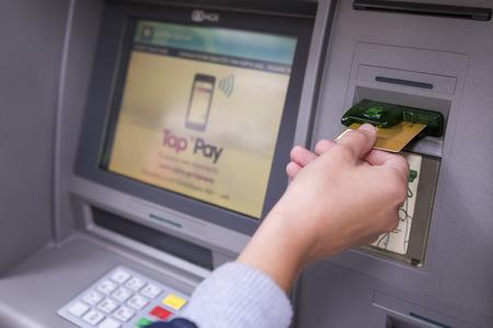 Thessaloniki, Griechenland, 27. Juni 2015: Die Menschen stehen in einer Warteschlange, um die Geldautomaten einer Bank nutzen. Person, die Geld aus dem Geldautomaten.