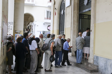 allow: THESSALONIKI, GREECE, JULY, 1 2015: Pensioners queue outside a National Bank branch as banks only opened for the retired to allow them to cash up to 120 euros in Athens