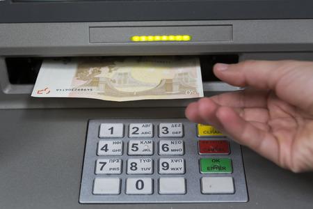 cuenta bancaria: Tesalónica, Grecia, 27 de junio 2015: La gente coloca en una cola para utilizar los cajeros automáticos de un banco. Persona que recibe dinero del cajero automático.