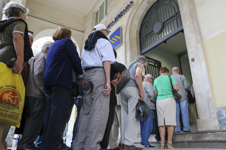the sovereign: THESSALONIKI, GREECE, JULY, 1 2015: Pensioners queue outside a National Bank branch as banks only opened for the retired to allow them to cash up to 120 euros in Athens
