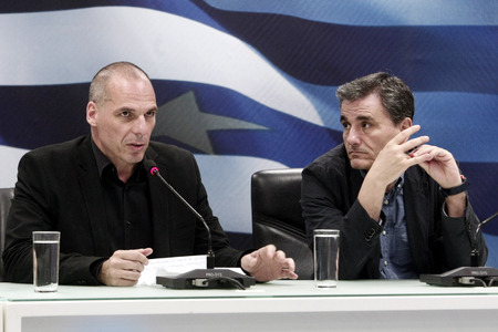 l hand: ATHENS, GREECE - JULY 6, 2015: Outgoing Greek Finance Minister Yanis Varoufakis (L) speaks as the new Finance Minister Euclid Tsakalotos (R) listens to him during a hand over ceremony