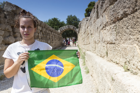 ruins is ancient: Olympia, Greece- August 9, 2015: Girl holds the Brazilian flag for the next sports competitions at Olympia birthplace of the sports competition games, in Greece.