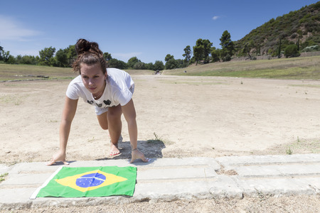 ancient olympic games: Olympia, Greece- August 9, 2015: Girl ready to run with the Brazilian flag for the next Olympics at Olympia, birthplace of the Olympic games, in Greece. Editorial
