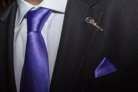 bespoke: Man in black suit with purple tie and broach