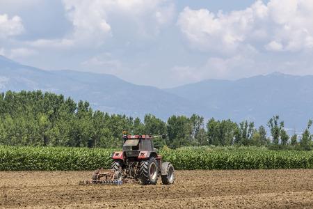 fertile: Thessaloniki, Greece - June 21, 2015: A tractor working planting wheat in the fertile farm fields of Greece Editorial