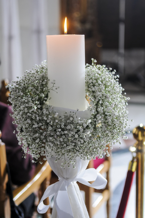 christian candle: White candles and carnations flower wedding decoration in a church