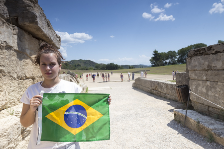 ancient buildings: Olympia, Greece- August 9, 2015: Girl holds the Brazilian flag for the next Olympics at Olympia birthplace of the Olympic games, in Greece.