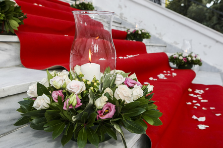 church flower: Wedding red carpet with white candles in church stairs