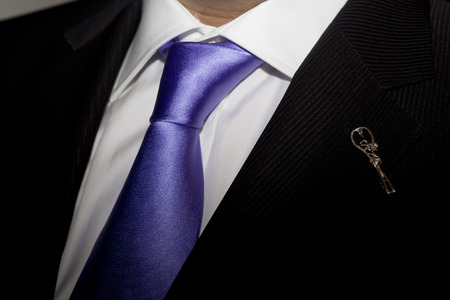 broach: Man in black suit with purple tie and broach