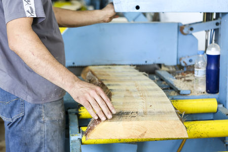 mitre: Thessaloniki, Greece, July 8, 2015: Craftsmen cut a piece of wood at a woodworking factory in Greece. Wood and furniture production plant, industrial factory with tools and objects.