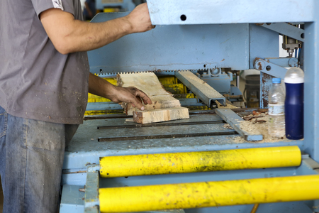 crosscut: Thessaloniki, Greece, July 8, 2015: Craftsmen cut a piece of wood at a woodworking factory in Greece. Wood and furniture production plant, industrial factory with tools and objects.