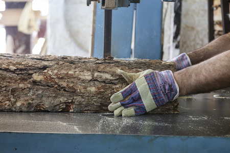 assemblies: Thessaloniki, Greece, July 8, 2015: Craftsmen cut a piece of wood at a woodworking factory in Greece. Wood and furniture production plant, industrial factory with tools and objects.