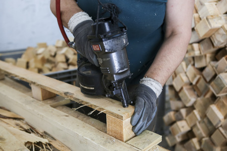 crosscut: Thessaloniki, Greece, July 8, 2015: Craftsman puts nails in a piece of wood at a woodworking factory in Greece. Wood and furniture production plant, industrial factory with tools and objects.