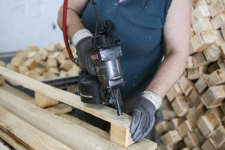 assemblies: Thessaloniki, Greece, July 8, 2015: Craftsman puts nails in a piece of wood at a woodworking factory in Greece. Wood and furniture production plant, industrial factory with tools and objects.