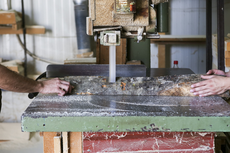 Thessaloniki, Greece, July 8, 2015: Craftsmen cut a piece of wood at a woodworking factory in Greece. Wood and furniture production plant, industrial factory with tools and objects.