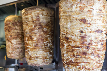meat grilled: A pair of rotating skewered chicken and lamb meat grilled and ready to serve in a typical Middle Eastern sandwich Stock Photo