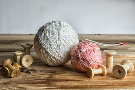 old spools: Spools of thread on wooden  background. Old sewing accessories. Stock Photo