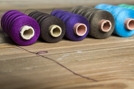 old spools: Spools of thread on wooden background. Old sewing accessories. colored threads