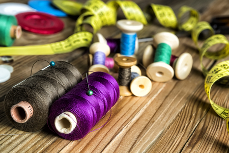 sewing supplies: Sewing Supplies, Spools of thread, Buttons, Scissors, Measuring tape. On Wooden Background.