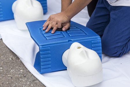 chest compression: man instructor showing CPR on training doll