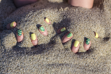 Female hand with beautiful nail polish playing with sand
