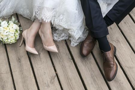 bröllop: fötter brud och brudgum, bröllop skor (mjukt fokus). Cross bearbetade bilden för vintagelook Stockfoto