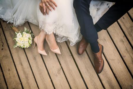 fötter brud och brudgum, bröllop skor (mjukt fokus). Cross bearbetade bilden för vintagelook Stockfoto
