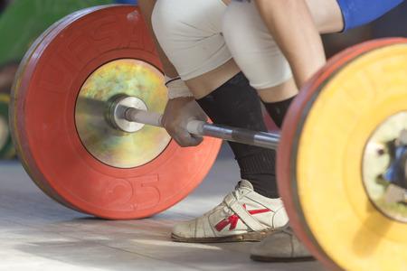 levantar pesas: Sal�nica, Grecia 3 de octubre de 2015: Las manos y los pies de atleta en la barra. Atleta joven que se prepara para levantar pesas durante el Campeonato de Halterofilia griega