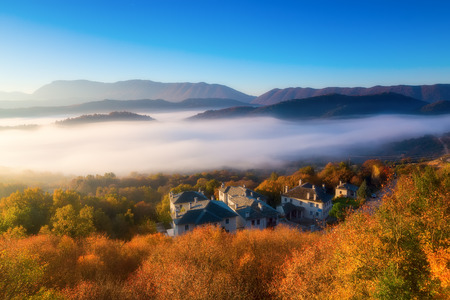 autumn scenery up early with fog in Zagorochoria, Epirus Greece (soft focus). Cross processed image for vintage look Stock Photo