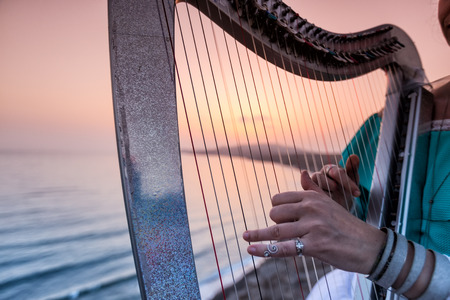 Close up of the hands of woman playing harp by the sea at sunset in Santorini, Greece
