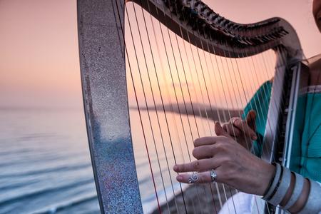 Nahaufnahme von den Händen der Frau spielt Harfe durch das Meer bei Sonnenuntergang in Santorini, Griechenland