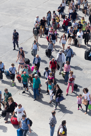 accepts: Paros, Greece, May 17, 2015: Passengers board the ship at the port of Paros in Greece.The Paros is an island in Cyclades that accepts too many tourists every year Editorial
