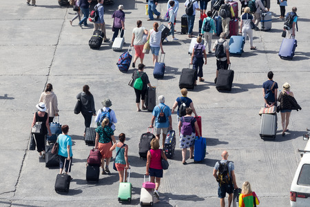 disembark: Paros, Greece, May 17, 2015: Passengers disembark from the ship at the port of Paros in Greece .The Paros is an island in Cyclades that accepts too many tourists every year