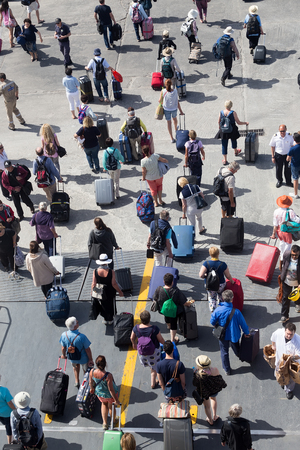 too many: Paros, Greece, May 17, 2015: Passengers disembark from the ship at the port of Paros in Greece .The Paros is an island in Cyclades that accepts too many tourists every year