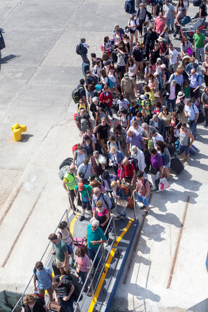 embark: Paros, Greece, May 17, 2015: Passengers board the ship at the port of Paros in Greece.The Paros is an island in Cyclades that accepts too many tourists every year Editorial