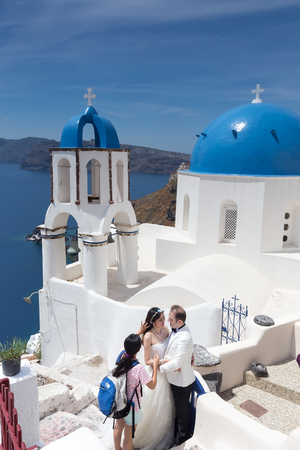 get across: Oia, Santorini, Greece- May 13, 2015: A couple of newlywed's tourists in front of church with the view of Santorini island, in Greece. Tourists come across the world to get married in Santorini.