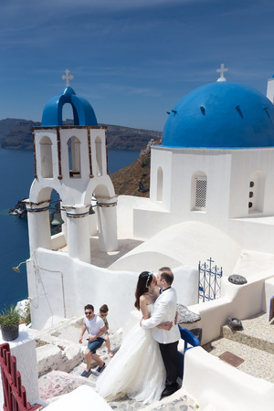 get across: Oia, Santorini, Greece- May 13, 2015: A couple of newlywed's tourists in front of church with the view of Santorini island, in Greece. Tourists come across the world to get married in Santorini. Editorial
