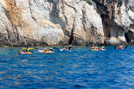 cano: Zakynthos, Greece - August 11, 2015: Tourists enjoying the clear water in their canoes at Zakynthos island, in Greece. Navagio Beach is a popular attraction among tourists visiting the island of Zakynthos