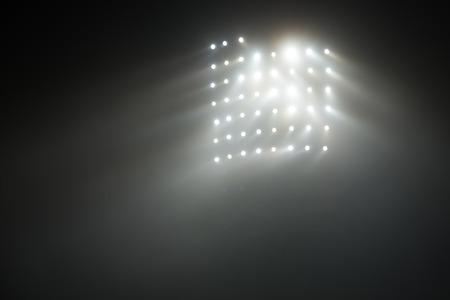 floodlit: Bright white and yellow Stadium lights with fog Stock Photo