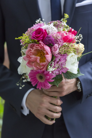 welldressed: well-dressed man holding a bouquet of flowers. Holidays and celebrations. Wedding day. Stock Photo