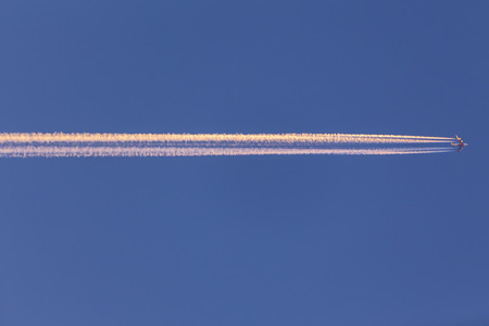 contrail: Airplane with contrail high in the sky at sunset Stock Photo