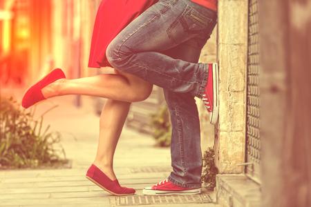 Junges Paar küssen im Freien. Männliche und weibliche Beine. Cross verarbeitet Bild für Vintage-Look