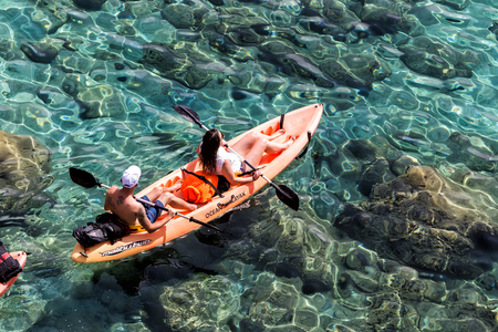 Milos, Greece - September 10, 2015: Tourists kayaking at Tsigrado Beach in Milos island, Cyclades, Greece