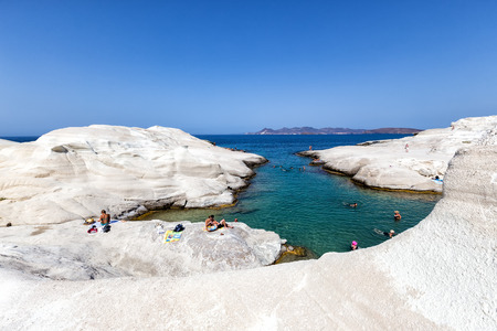 in particular: Milos, Greece - September 9, 2015: Tourists enjoy the clear water of Sarakiniko beach in Milos, Greece. This beach is one of the most beautiful beaches of Milos and surely the most particular one.