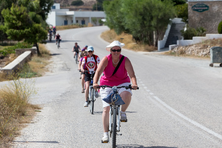 to prefer: Milos, Greece - September 10, 2015: People going by bike in the city in Milos, Greece. A lot of tourists prefer using bike instead of car or bus to move around the city. Editorial