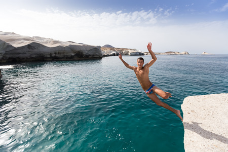 in particular: Milos, Greece - September 9, 2015: Tourists jump in the clear water of Sarakiniko beach in Milos, Greece. This beach is one of the most beautiful beaches of Milos and surely the most particular one.