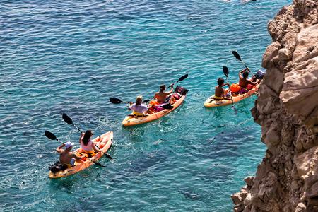 Milos, Greece - September 10, 2015: Tourists kayaking at Tsigrado Beach in Milos island, Cyclades, Greece
