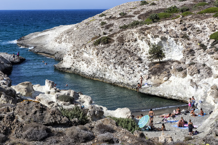kyklades: Milos, Greece - September 8, 2015: Tourists enjoy the clear water of the beautiful beach in Milos island, Cyclades, Greece