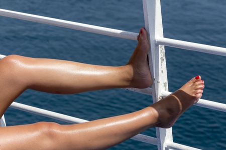 painted toes: Bare woman feet on deck by the ocean Stock Photo