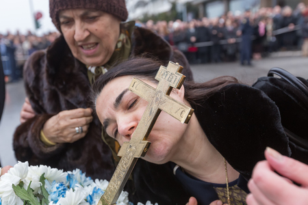 retrieved: Thessaloniki, Greece, January 6, 2016: A woman kisses a wooden cross retrieved from the sea during the blessing of the water ceremony marking the Orthodox Epiphany Day